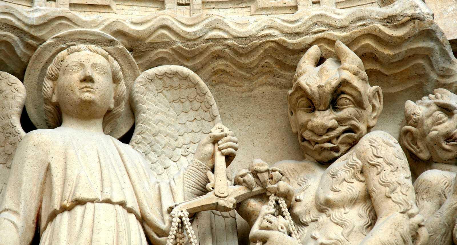 Ange et démon sur la façade de Notre-Dame de Paris